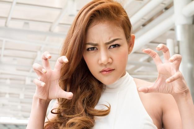 Расстроенная, сердитая женщина готова причинить тебе боль когтями