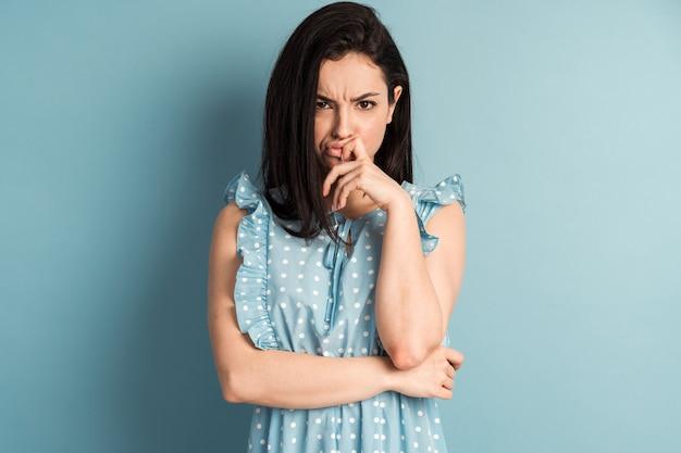 青い壁に分離された美しい水玉模様のドレスで動揺、怒っている若い女性