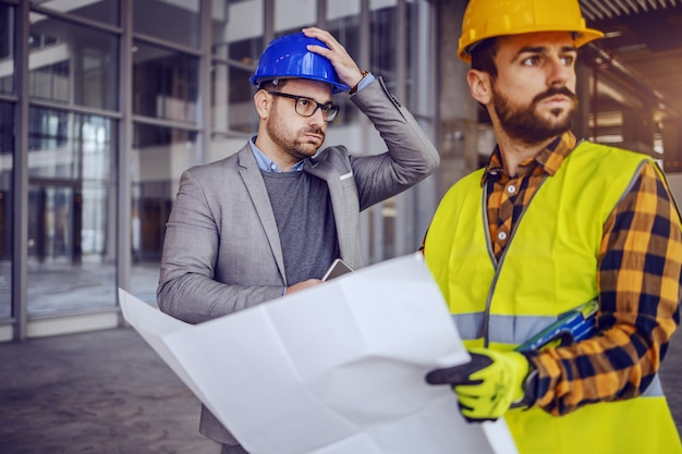 Upset architect holding his head and thinking about mistake he made on blueprints. construction worker holding blueprints and looking away.