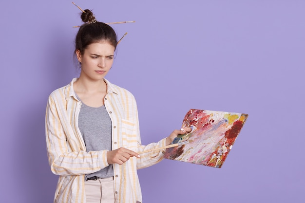 Upset artist holding picture and looking at it with upset facial expression, posing against lilac studio wall