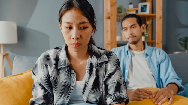 Upset asian couple sit on couch in living room