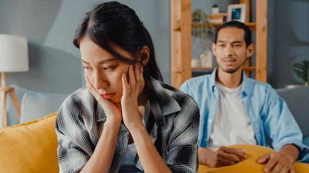 動揺したアジアのカップルは、リビングルームのソファに座る