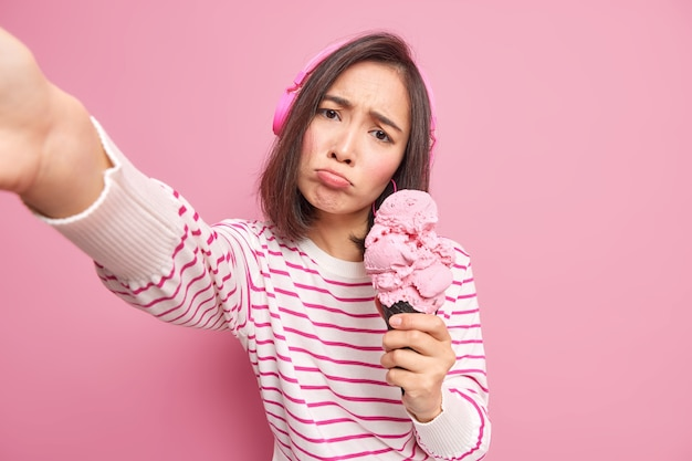 Upset asian teenage girl tilts head looks sadly makes selfie portrait holds yummy ice cream tilts head listens music via wireless headphones dressed in striped jumper isolated over pink wall