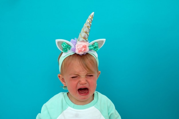 Upset baby with open mouth and eyes closed in unicorn costume crying on blue