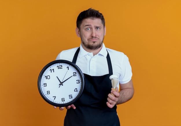 オレンジ色の背景の上に立っている悲しい表情でカメラを見て壁時計とシェービングブラシを保持しているエプロンで動揺した理髪店の男