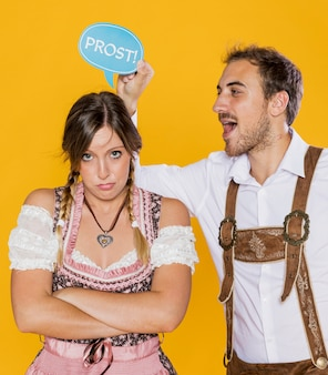 Upset bavarian woman and man holding a sign