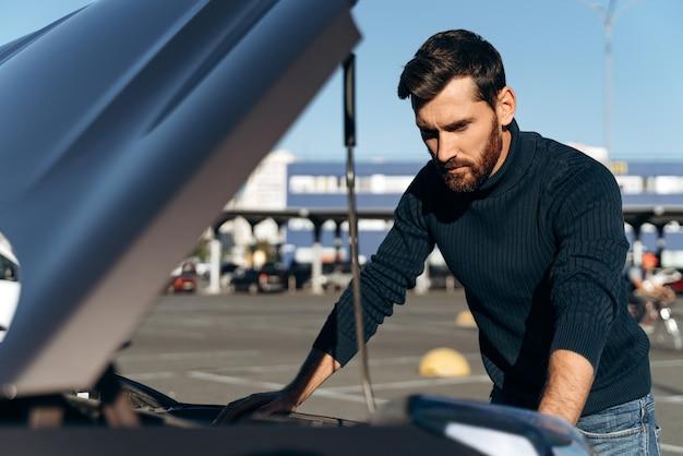화가 난 수염 난 남자가 도로에서 고장난 후 자동차 엔진을 확인했습니다. 진지한 남성이 오프닝 후드 앞에 서 있습니다. 교통 개념