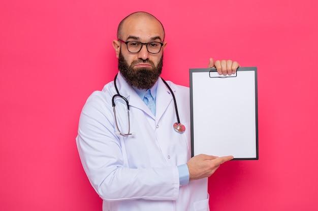 Расстроенный бородатый мужчина-врач в белом халате со стетоскопом на шее в очках, держит буфер обмена с пустыми страницами, смотрит с грустным выражением лица, поджимая губы