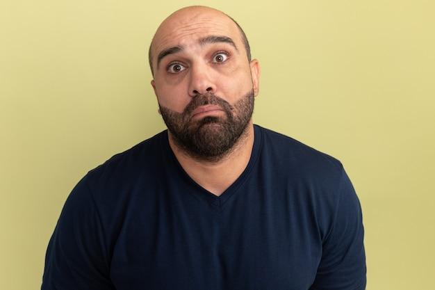 緑の壁の上に立っている悲しい表情と黒のtシャツで動揺したひげを生やした男