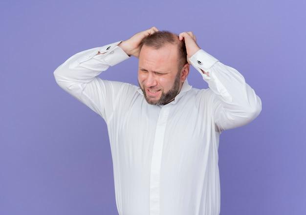 그의 머리를 만지고 흰색 셔츠를 입고 화가 수염 난된 남자가 파란색 벽 위에 서 좌절