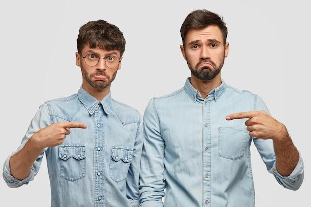 Due uomini barbuti sconvolti aggrottano le sopracciglia con dispiacere, si indicano a vicenda, litigano, discutono su chi dovrebbe pulire la macchina, stanno da vicino in abiti eleganti di jeans, isolati su un muro bianco. è colpevole!