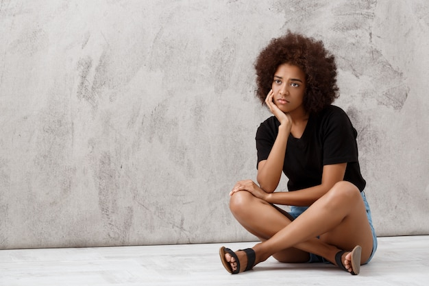 Upset beautiful african girl sitting over light wall.