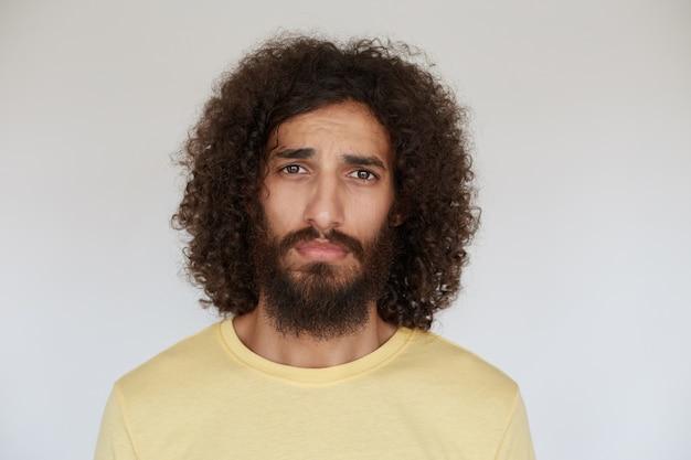 검은 곱슬 머리가 슬프게 보이고 그의 입술을 접은 채 캐주얼 한 옷에 서있는 아름다운 갈색 눈을 가진 젊은 수염 난 남자를 화나게합니다.