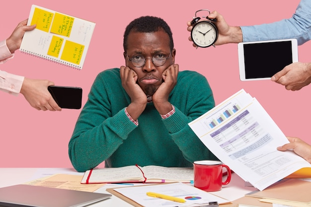 Upset black male worker has much work, thinks about business project, being lack of time