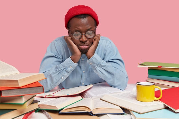 Upset black young man focused down, feels depressed and sad as reads books for long time, wears round spectacles, red hat and shirt