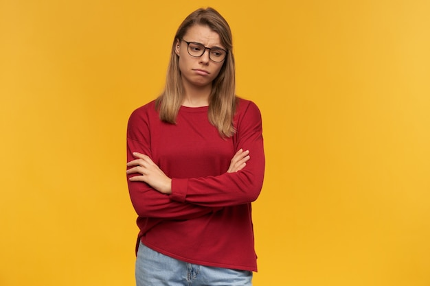 Upset blonde girl wearing glasses puffed out cheeks looking down to the right corner standing with arms folded isolated