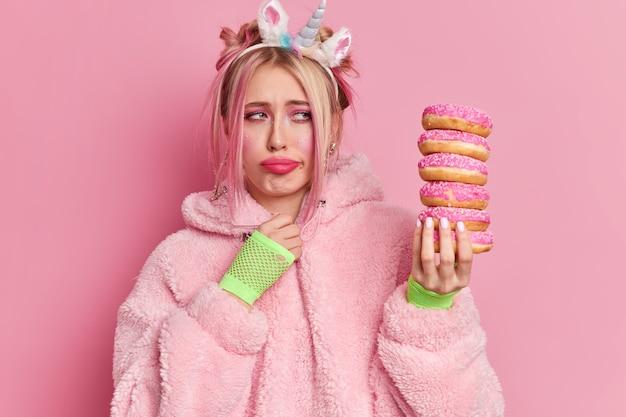Расстроенная блондинка с ярким макияжем грустно смотрит на кучу вкусных пончиков и испытывает искушение съесть что-нибудь сладкое