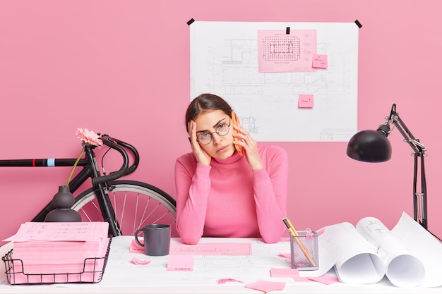 Upset bored woman tired of work prepares paper sketches has telephone conversation works on architect project wears round spectacles pink turtleneck poses at desktop surrounded with blueprints