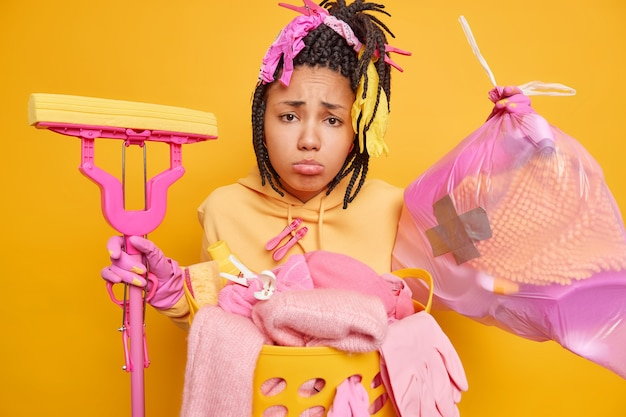 Upset bored young african american woman with dreadlocks collects rubbish in trash bag