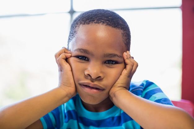 Расстроенный мальчик сидит в классе