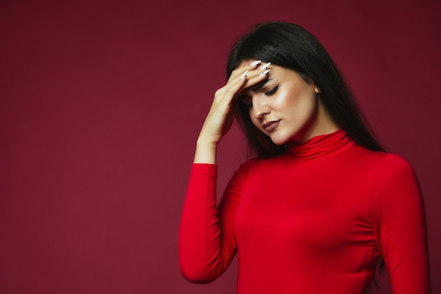 Upset brunette caucasian girl dressed in red pullover with annoying headache put hand on the forehead