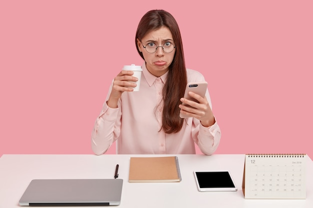Upset brunette female office perfectionist has unhappy expression, drinks takeaway coffee, holds mobile phone, wears round spectacles