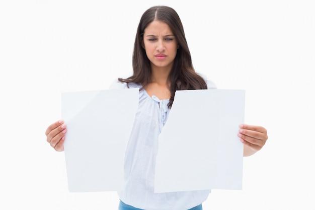 Upset brunette holding torn paper