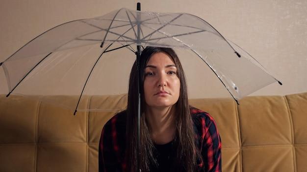 Расстроенная брюнетка-дама прячется от воды, текущей от соседей наверху под прозрачным зонтиком, сидя на диване в темной комнате крупным планом. понятие затопления квартиры и страхование имущества