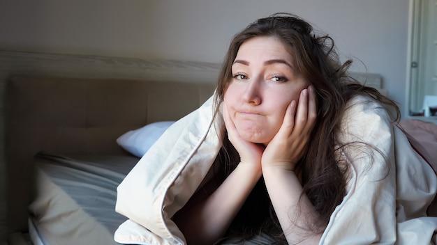 動揺したブルネットの長い髪の少女は、早朝のクローズアップで快適なホテルの部屋で自己隔離中に大きなベッドに横たわっています