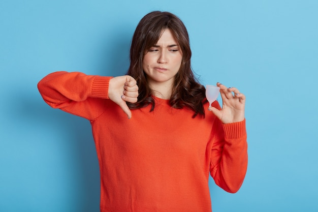 Upset brunette woman holds effective safe affordable menstrual product that do not suit her