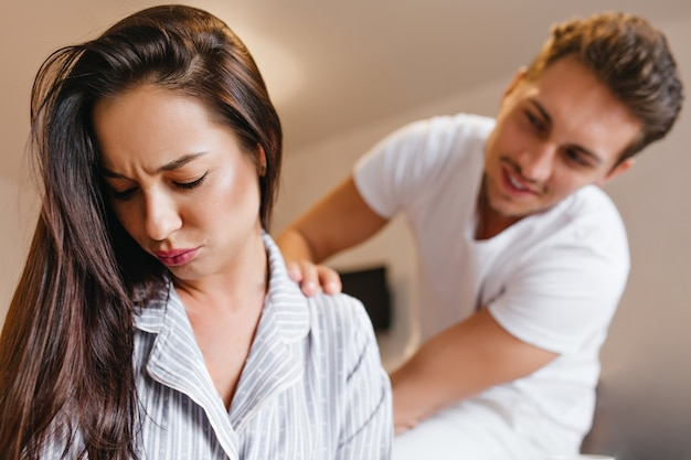 Upset brunette woman in pajama looking down while husband talk to her