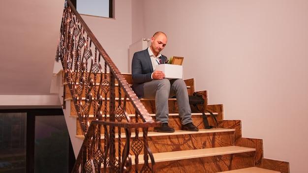 Расстроенный деловой корпоративный служащий, сидящий на лестнице с коробкой личных вещей, уволен из компании. группа профессиональных успешных бизнесменов, работающих в современном финансовом здании.