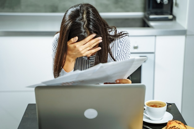 Upset business woman holding documents working on laptop at home.