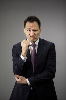 Расстроенный бизнесмен пытается остаться сильным во время финансового кризиса, серый