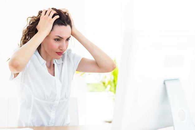 Upset businesswoman sitting at her desk