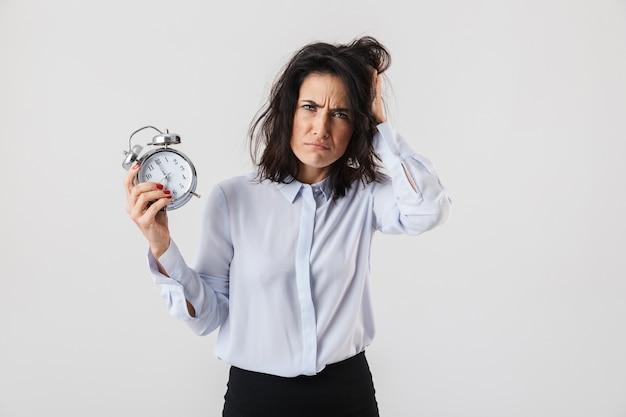 目覚まし時計を表示して、白い壁の上に孤立して立っているスマートな服を着て動揺した実業家