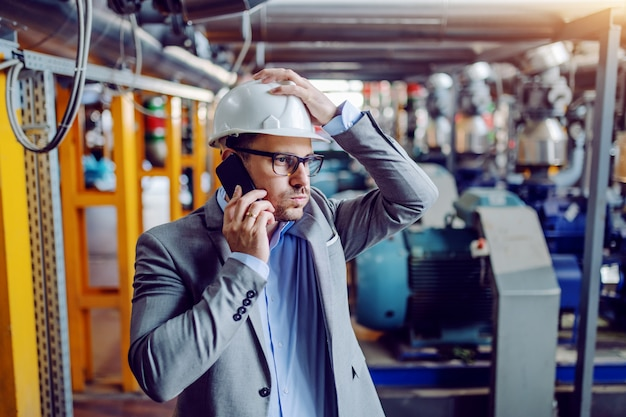 Upset caucasian businessman having phone call and holding his head while standing in power plant.