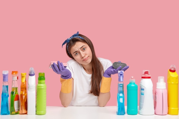 Upset caucasian woman tilts head, purses lips, holds sponge, surrounded with cleanser and other chemical supplies