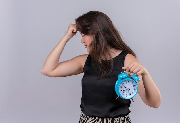 Расстроенная кавказская молодая девушка в черной майке держит будильник и положила руку на лоб на белом фоне