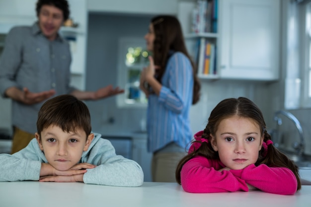 Upset children sitting while couple arguing with each other