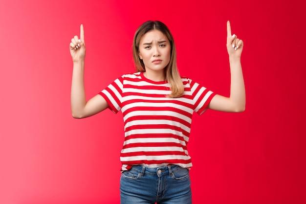 しかめっ面の悲しい、失望したポイントの指が泣き言を言って不平を言うしがみつくガールフレンドを動揺させ、苦情をスタンドストライプtシャツ赤い背景嫉妬深い友人がおいしいアイスクリームを食べて、また試してみたい