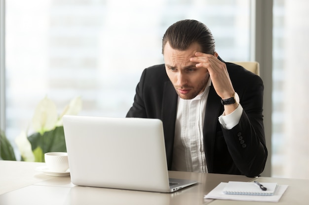 Upset confused businessman looking at laptop screen