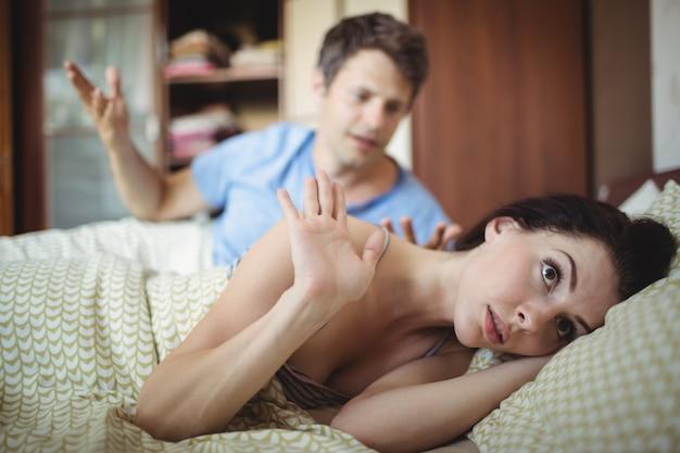 Расстроенная пара спорит друг с другом на кровати