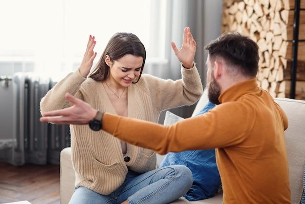 自宅でカップルを混乱させる。ハンサムな男と美しい若い女性がけんかをしています。一緒にソファーに座っています。家族の問題。