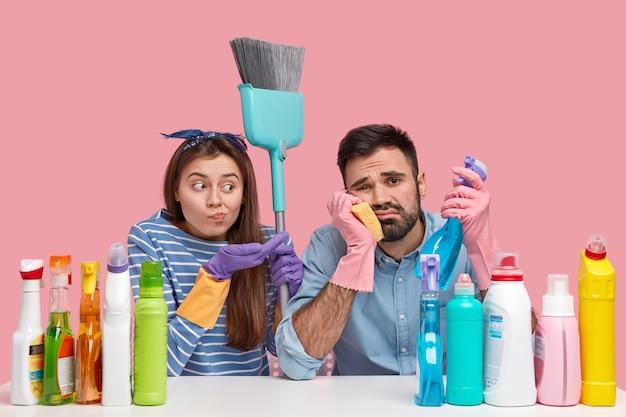 動揺したカップルは見た目が疲れていて、アパートで春の大掃除をし、洗剤とほうきを使い、カジュアルな服を着て、テーブルに座っています