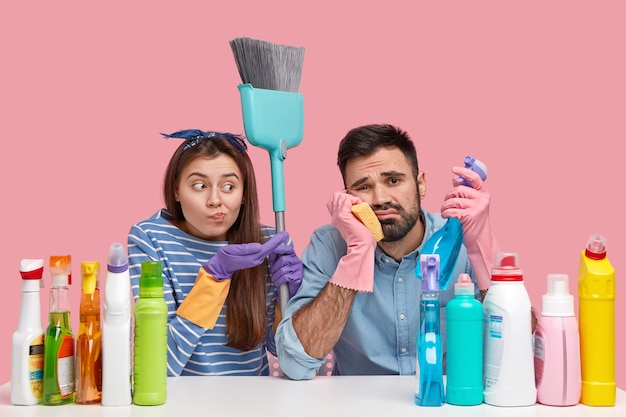Upset couple have tired looks, do spring cleaning in apartment, use detergents and broom, dressed in casual clothes, sit at table