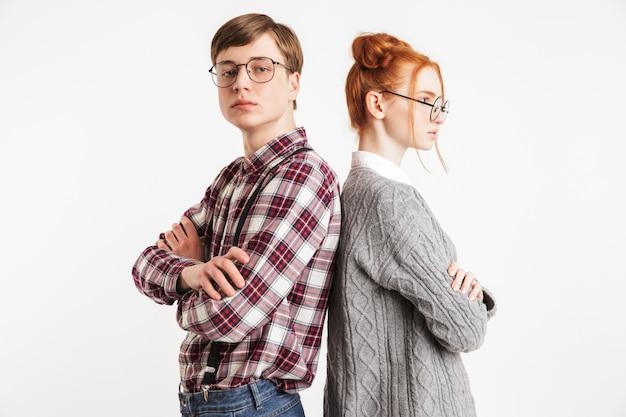 背中合わせに立っている学校のオタクの動揺のカップル