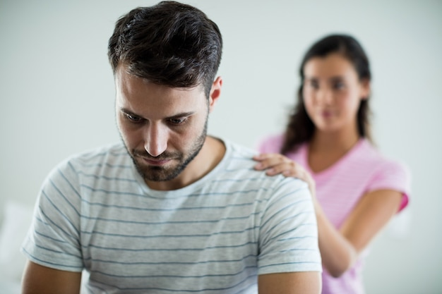 Upset couple sitting on bed in the bedroom at home