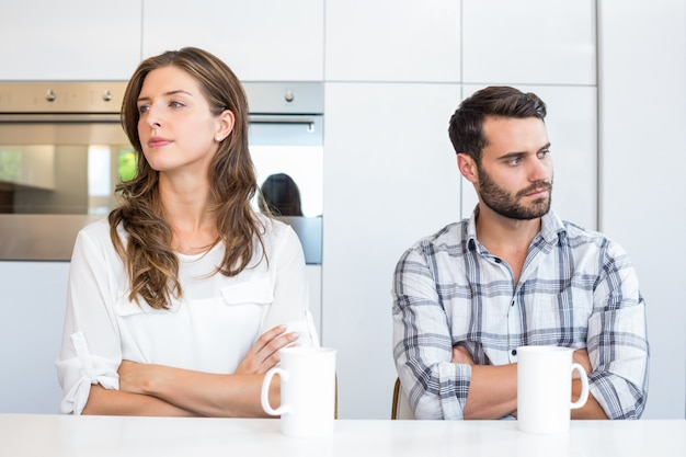 Upset couple sitting by table