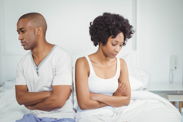 Upset couple not talking after argument sitting on bed